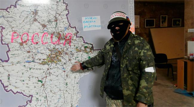 Сепаратист в здании указывает на карту донецкой области